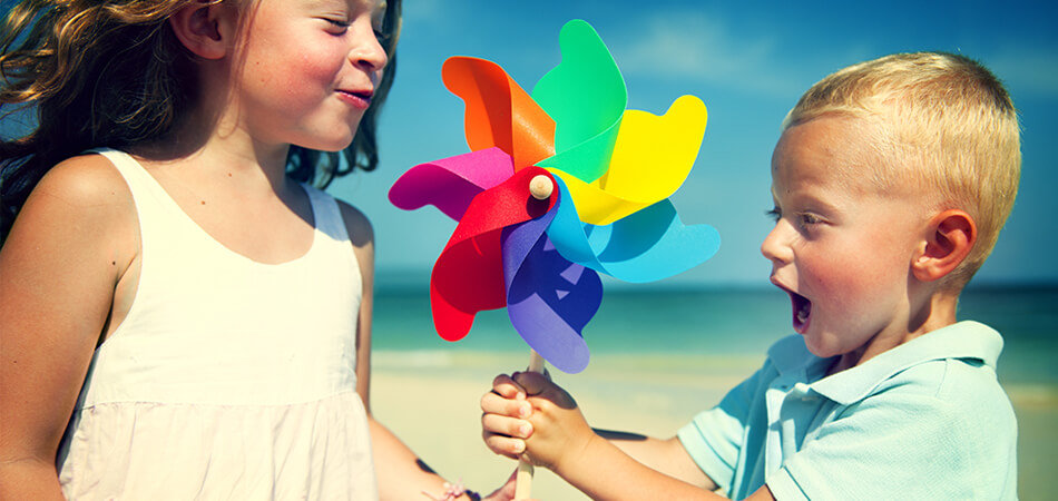 children holding rainbow spinning wheel on beach